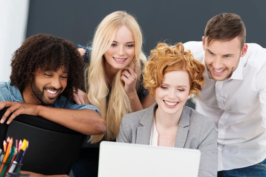 28756277 - successful business team with happy smiles grouped together around a laptop computer having a planning and strategy meeting