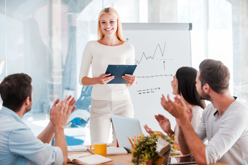 41179606 - great presentation! cheerful young woman standing near whiteboard and smiling while her colleagues sitting at the desk and applauding