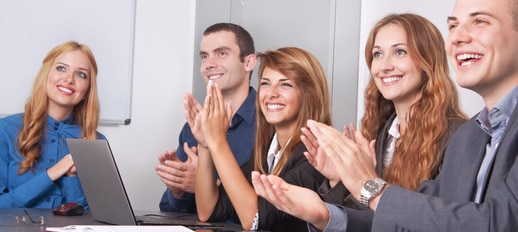 Five young business people applauding. The focus is on the girl on the right side.