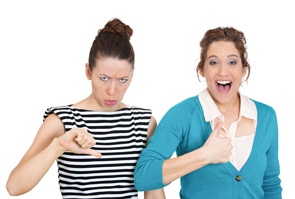 Closeup portrait, two young people, women. One being excited happy smiling, showing thumbs up, other serious, concerned, unhappy showing thumbs down, isolated white background. Emotion contrasts