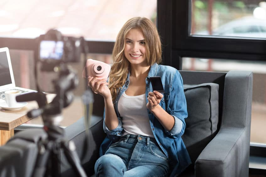 61352833 - modern blogger. cheerful delighted smiling woman sitting on the couch and feeling content while shooting a video
