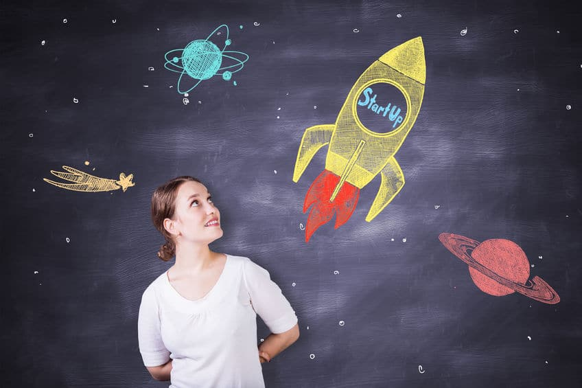 66718749 - cheerful caucasian female on chalkboard background with creative rocket ship sketch. startup concept