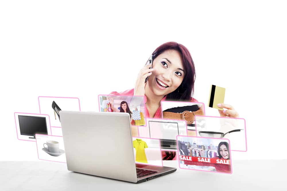 An attractive woman purchasing product online using her laptop computer, credit card, and mobile phone,