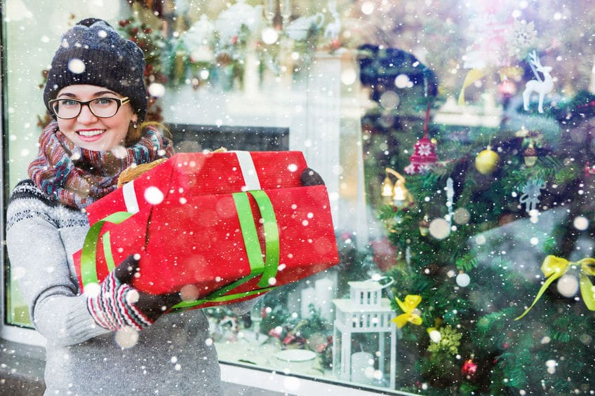 89629031 - woman with christmas gifts and purchases on a background of store window with new year decoration